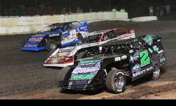 Three-wide action between Ryan Gustin (19R), Zack VanderBeek (33z) and Stormy Scott (2s) during the 3rd Annual USMTS Southern Kansas Nationals at the Caney Valley Speedway in Caney, Kan., on Tuesday, June 6, 2017.